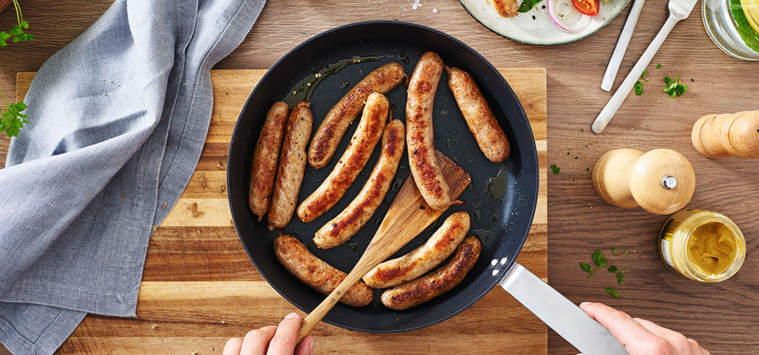 selbstgemachte Bratwurst in Bratpfanne auf Holztisch