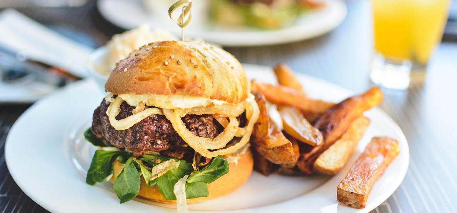 Hamburger mit Steak Fries auf einem weißen Teller. Rechts oben im Hintergrund steht ein Glas mit Orangensaft. Das Geschirr steht auf einem dunkelbraunen Holztisch.