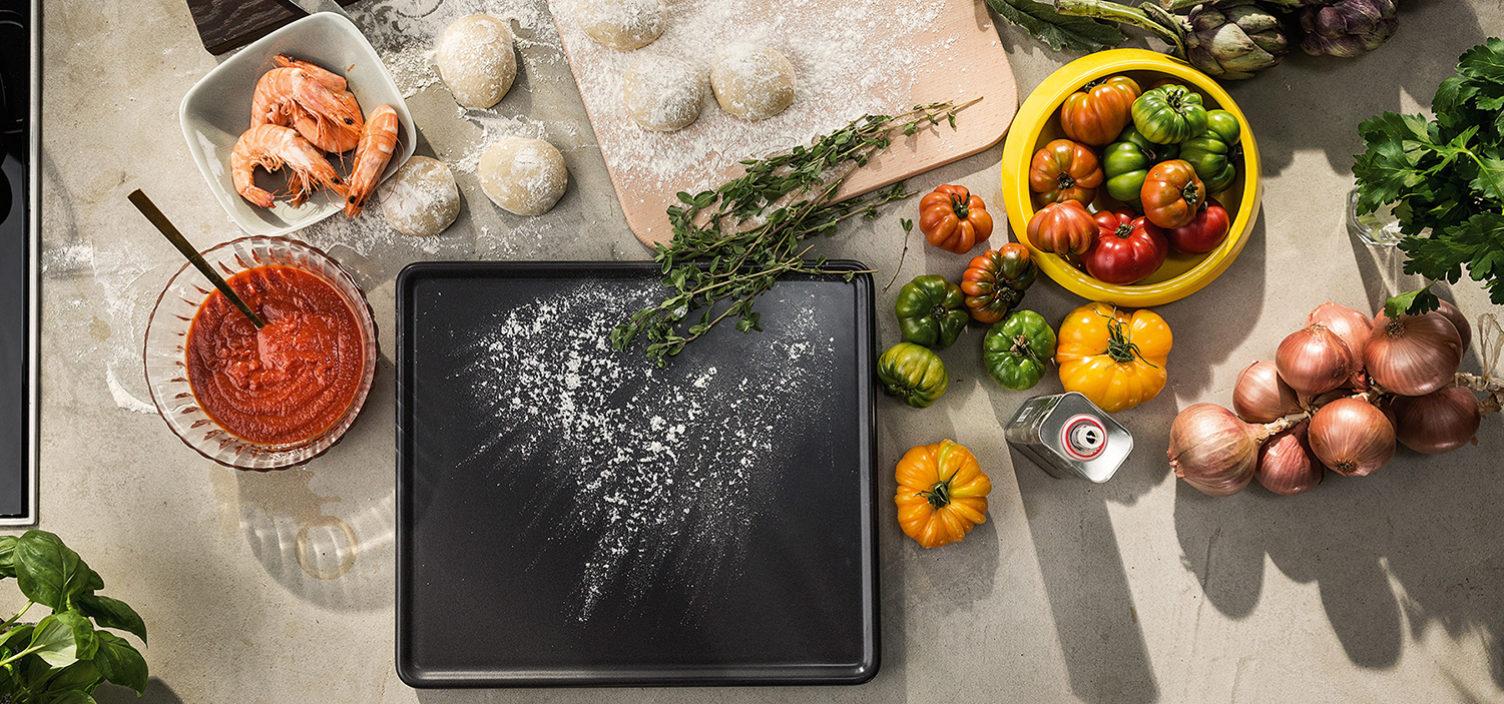 Backstein und Zutaten für die perfekte Pizza auf einem Tisch. Von links nach rechts: Glasschüssel mit Tomatensoße, Garnelen in weißer Schüssel, Pizzateig auf einem Holzbrett, grün, gelb und orange Paradeiser in einer gelben Schüssel und mehrere weiße Zwiebel. Mittig liegt der graue Backstein mit etwas Mehl bestaubt.