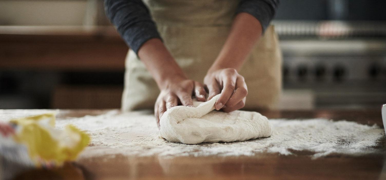 Person knetet Pizzateig auf Tisch
