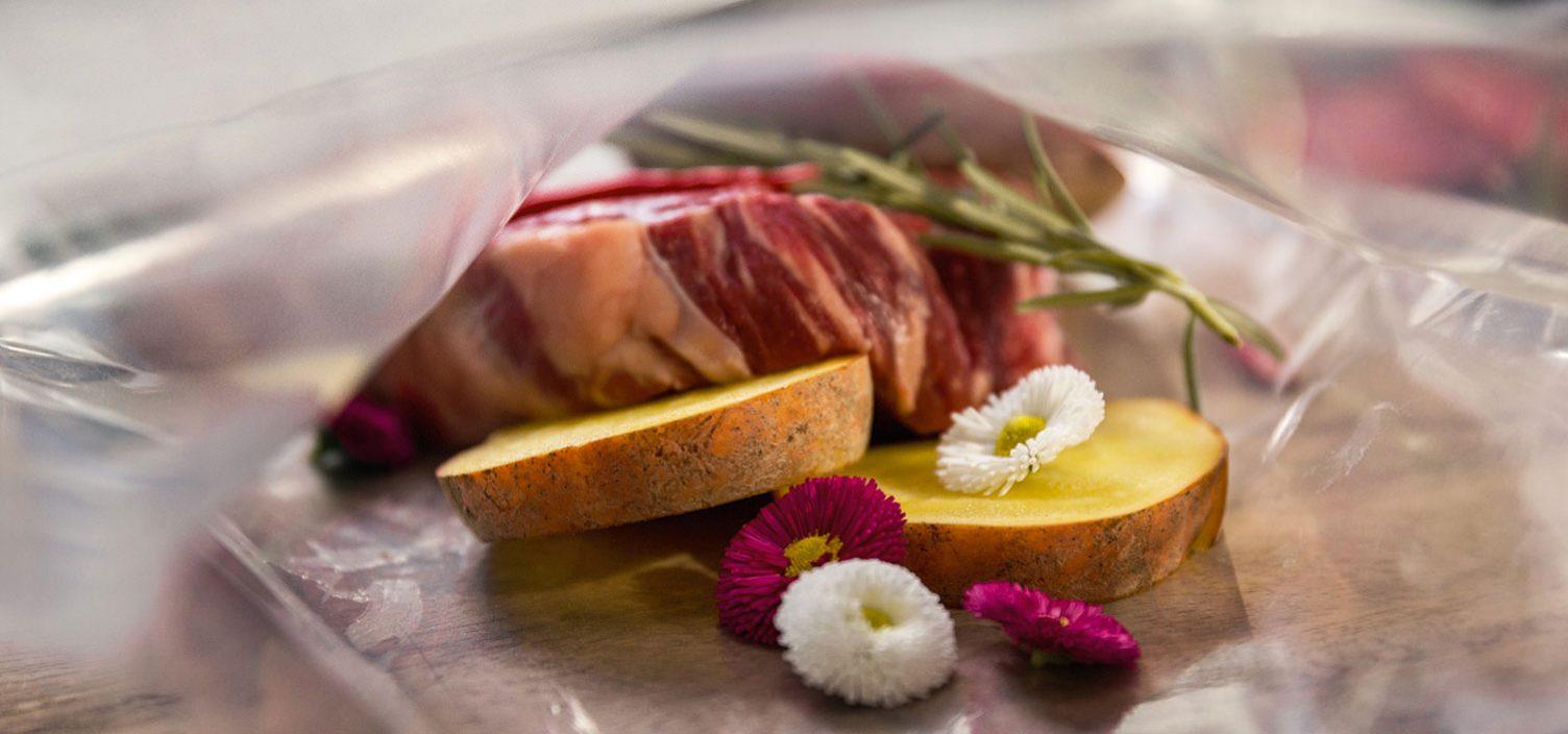 Nahaufnahme von Sous Vide Verpackung von Fleisch, Kartoffeln, Zwiebel und Blumen