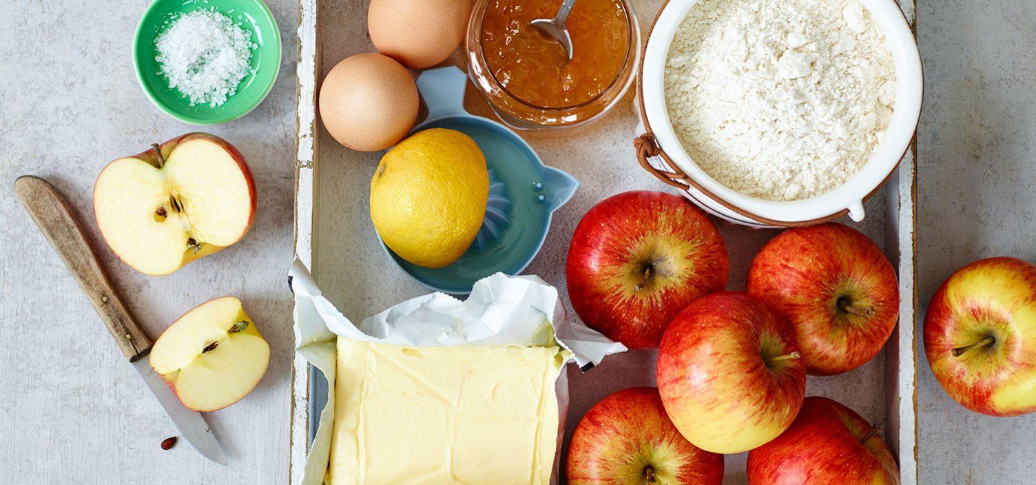 Zutaten für Apfelkuchen auf weißem Tisch