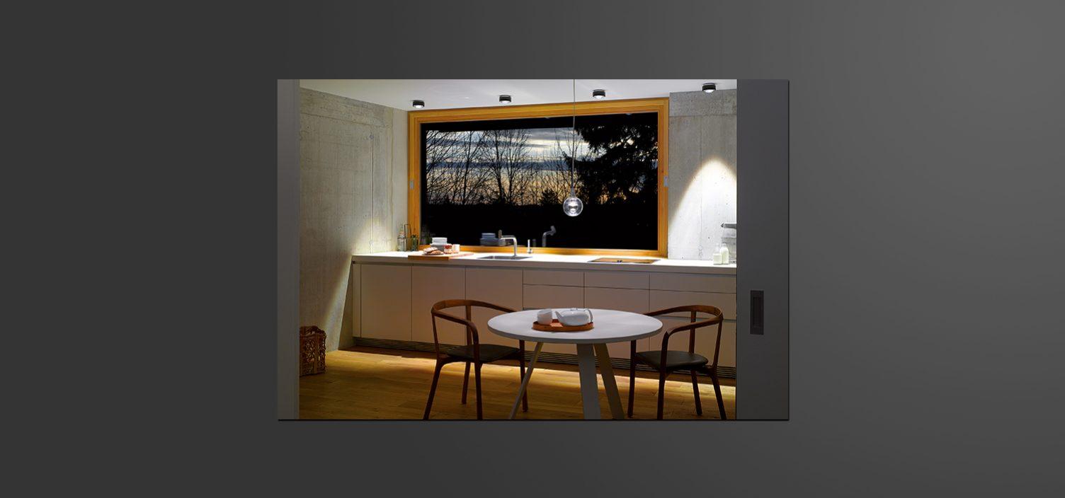 Kleiner runder weißer Tisch mit zwei Sesseln im Vordergrund. Dahinter eine weiße Küchenfront, spärlich beleuchtet mit einem Bild darüber. Auf dem Bild ist ein Wald in der Abenddämmerung zu sehen.
