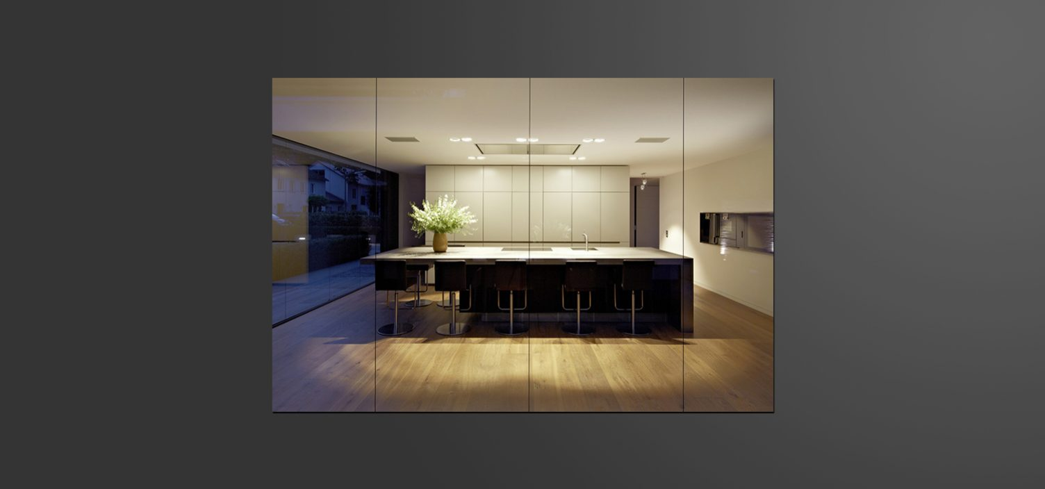 Aufnahme einer Kücheninsel in beige und anthrazit durch eine Glasfront.