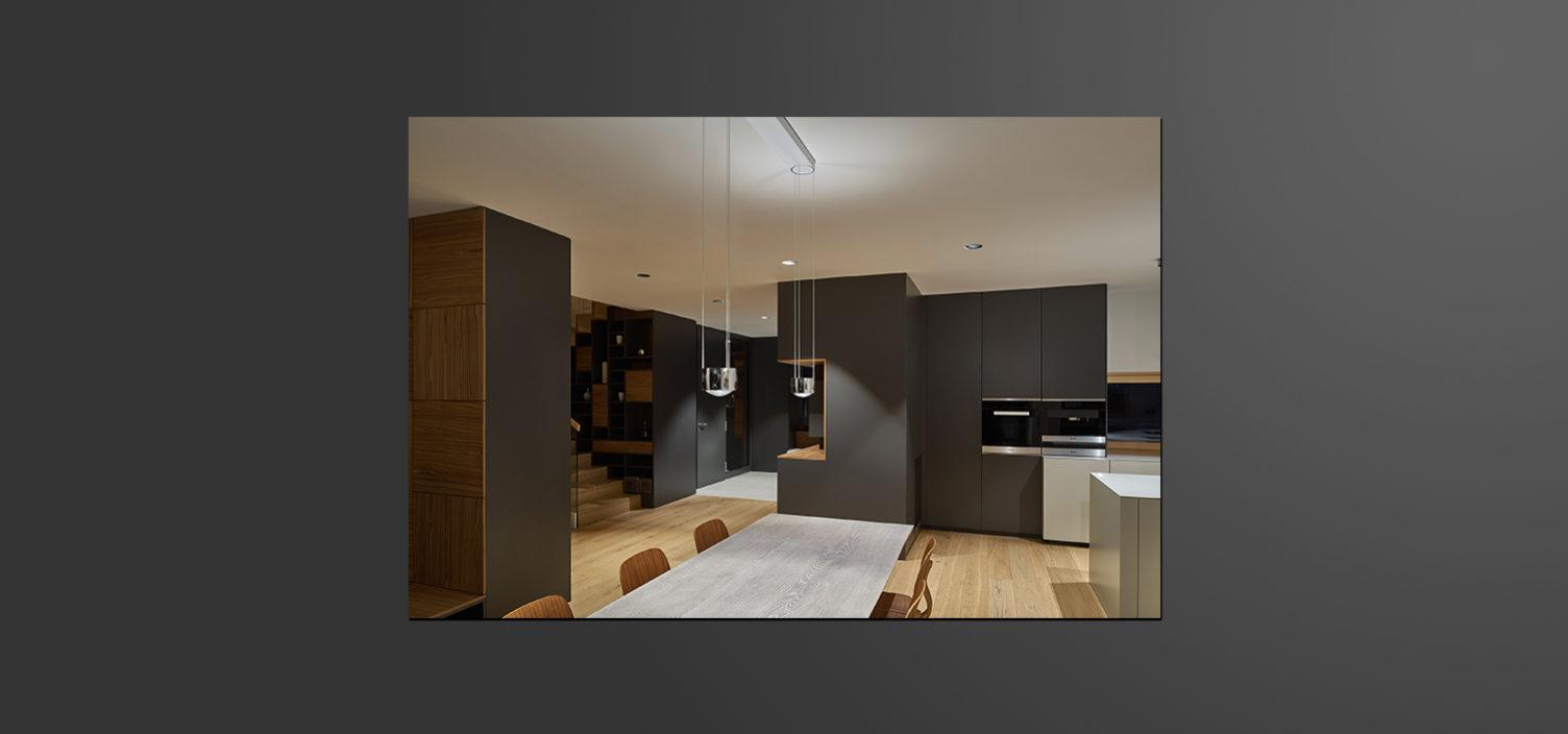 Im Vordergrund ist ein hellgrauer Tisch für sechs Personen mit Holzsesseln. Im Hintergrund ist eine Küchenzeile in anthrazit zu sehen sowie rechts im Bild ein Teil einer Kücheninsel in weiß. Im linken Hintergrund sieht man einen Stiegenaufgang in Holz.