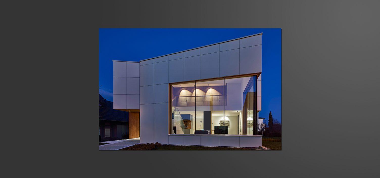 Seitenaufnahme eines kubischen Hauses mit großen weißen Außenplatten und Glasfront in Abenddämmerung. Durch die Glasfront sieht man einen hell beleuchteten Innenraum, der minimalistisch eingerichtet ist.
