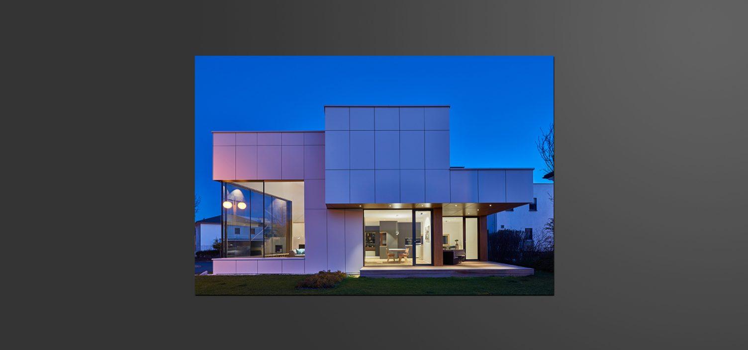 Kubisches Haus mit großen weißen Außenplatten und Glasfronten. Durch die Glasfronten sieht man einen hell beleuchteten Innenraum als Kontrast zur Abenddämmerung.