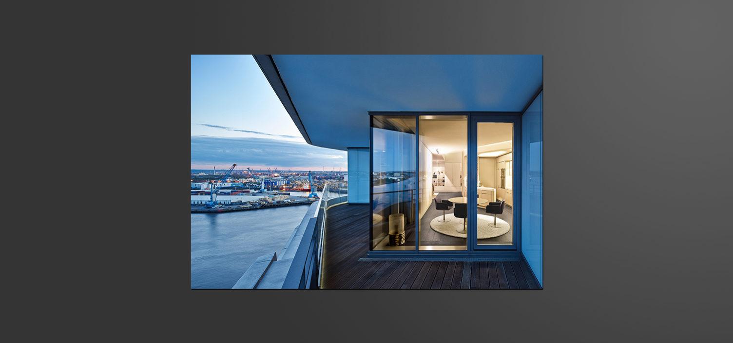 Durch eine Glasschiebetür sieht man in einen hell beleuchteten Wohnraum in beige. Auf der linken Seite sieht man Wasser, sowie einen Hafen und in der Ferne eine Stadt.