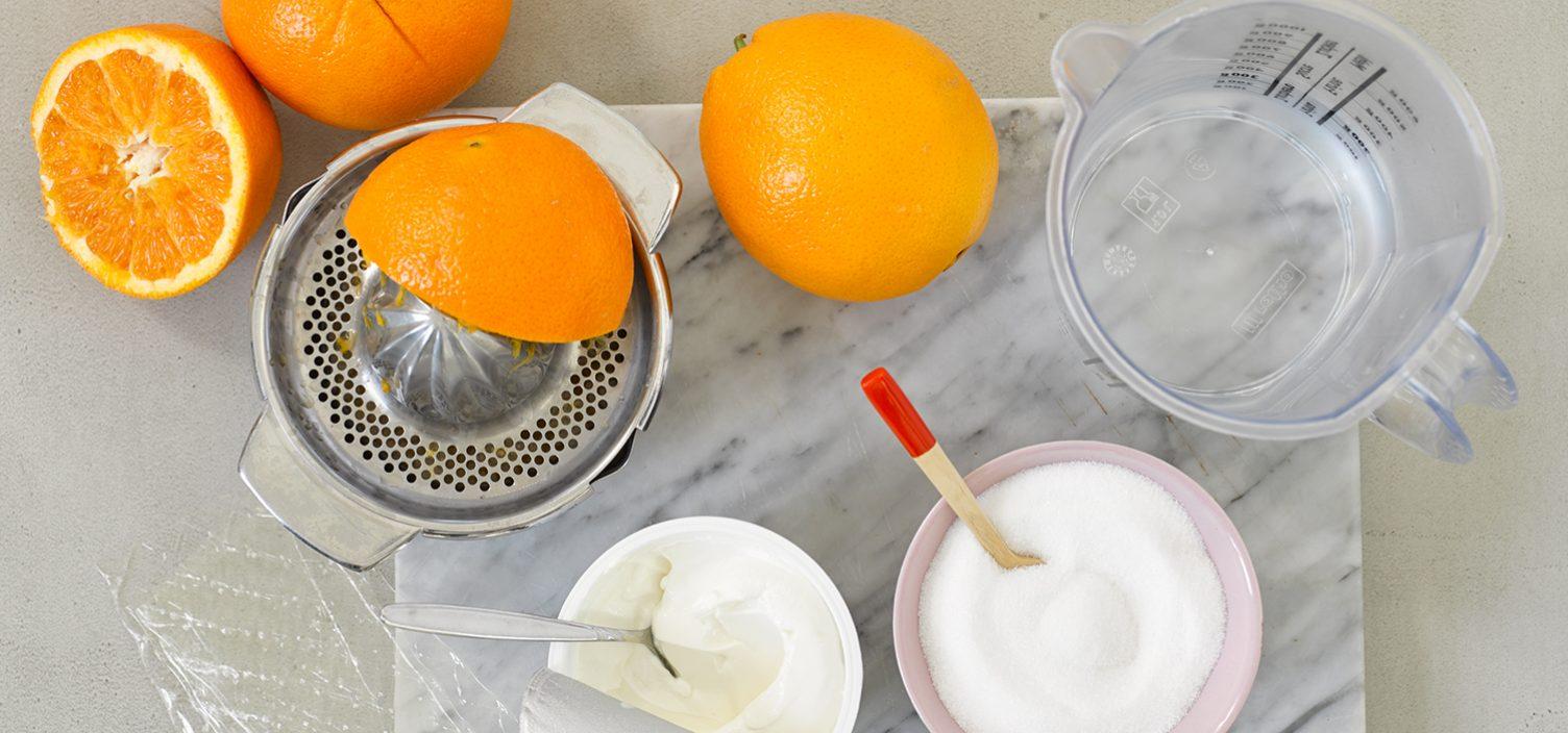 Top-Shot von Zutaten für Orangensorbet: halbierte und ganze Orangen links oben im Bild, darunter zwei Schalen mit Zucker und Schlagobers. Rechts oben im Bild ein Messbecher aus Plastik.