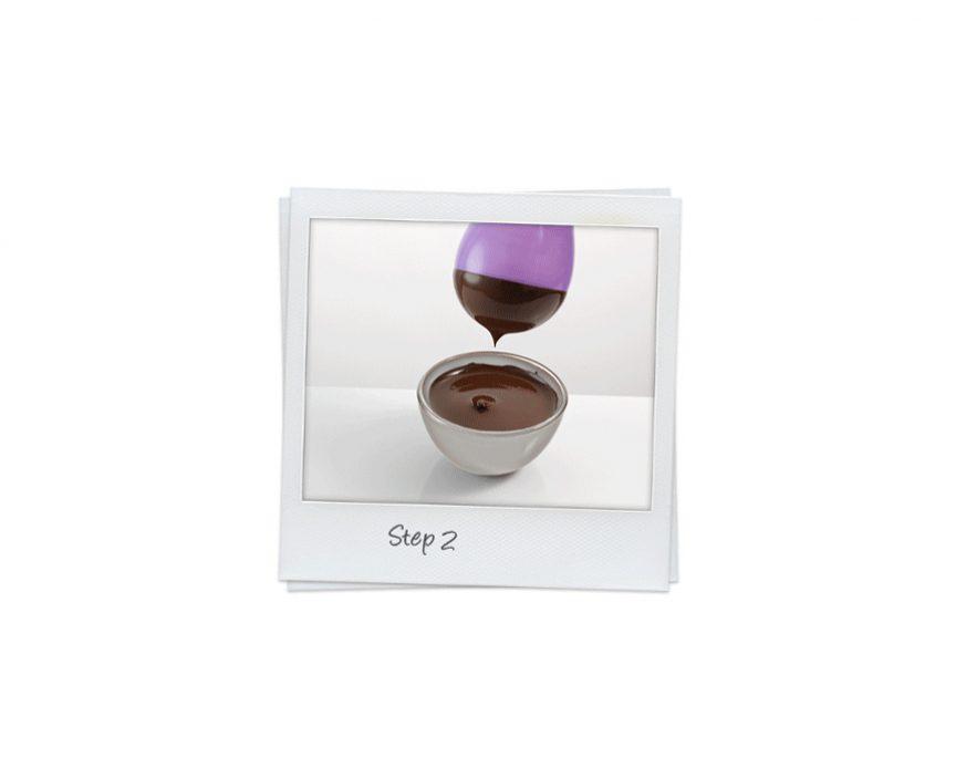 Polaroid in weiß mit Schüssel, die mit flüssiger Schokolade gefüllt ist. Darüber ein lila Luftballon der zur Hälfte mit Schokolade bedeckt ist.