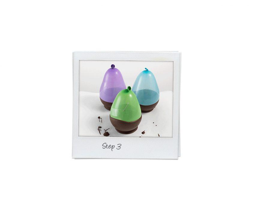 Polaroid in weiß mit drei Luftballons in lila grün und blau, die zur Hälfte mit Schokolade bedeckt sind.