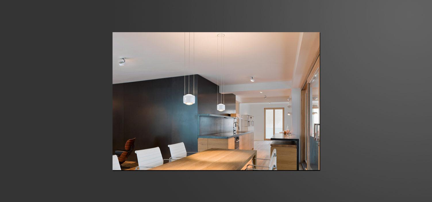 Im Vordergrund sieht man einen Teil eines Holztisches mit weißen Stühlen. Im Hintergrund ist eine Wand in anthrazit sowie eine Küche in Holz und Arbeitsplatte in anthrazit.