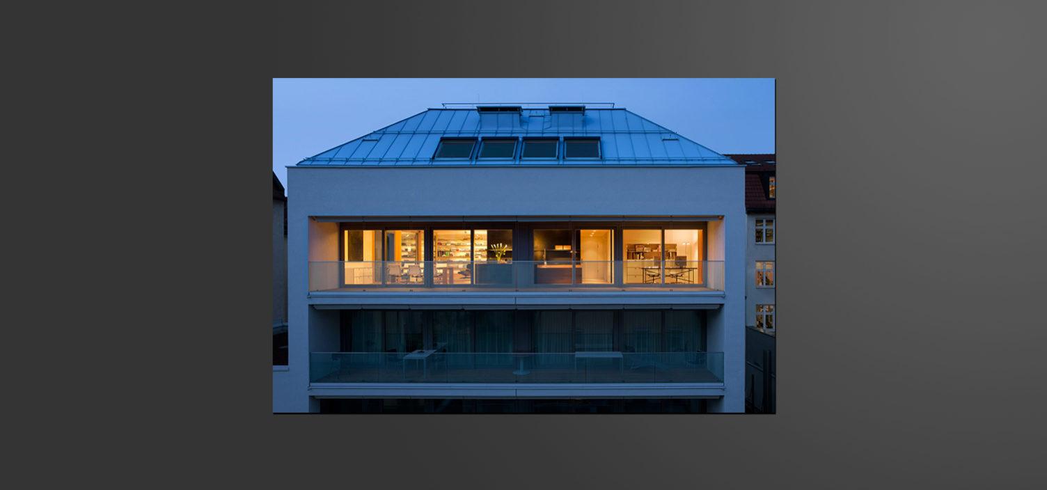 Außenaufnahme von einem Wohnhaus mit Fokus auf das oberste Wohngeschoss mit Außenterasse mit Glasfront. Die oberste Wohnung ist beleuchtet, während in der Wohnung darunter im Bild kein Licht brennt.
