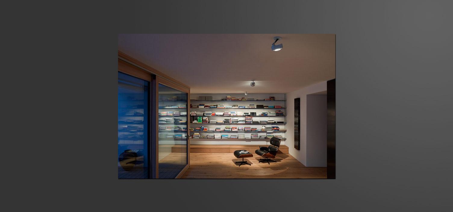 Auf der linken Seite ist eine Glasschiebetür mit braunem Rahmen. Mittig rechts steht ein Wohnzimmersessel aus Leder auf einem Holzboden. Hinter dem Sessel ist ein bunt befülltes Regal zu sehen.